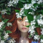 髪 セット 崩れる 前髪 緑に隠れる女性 白い花が咲いている