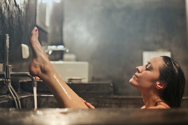 髪 乾きにくい ベタベタ 多い 猫っ毛 前髪 お風呂に入っている女性 足を上げている