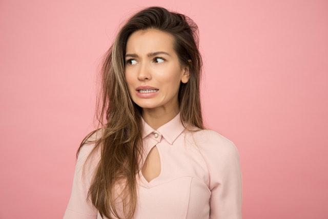 パーマ とれる 早い シャンプー 髪質 判断 ショックを受けた顔 背景がピンク